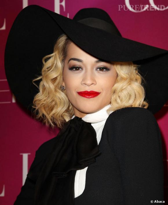 Rita Ora se fait fatale sous sa capeline avec sa bouche rouge et ses cils de poupée.