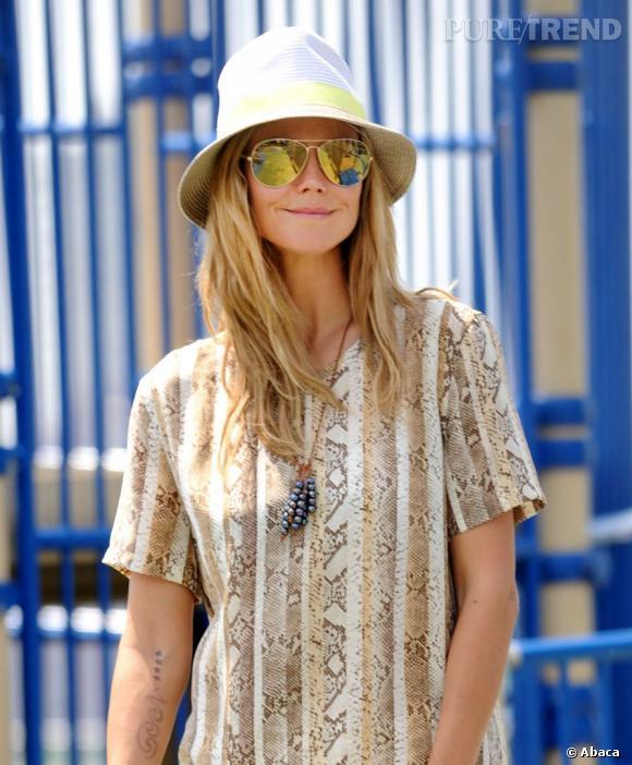 Heidi Klum ensoleillée des pomettes jusqu'aux pointes de cheveux sous son chapeau beige.