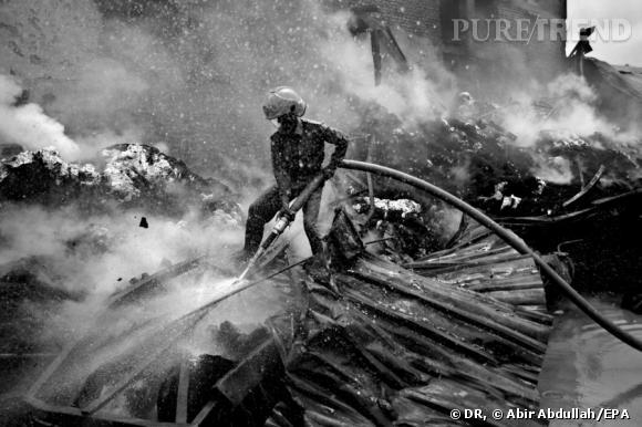 Un pompier tente d'éteindre un incendie à l'usine de Kung Keng. Les conditions de travail dangeureuses ont provoqué de nombreux accidents. Zone industrielle, 6 août 2005.