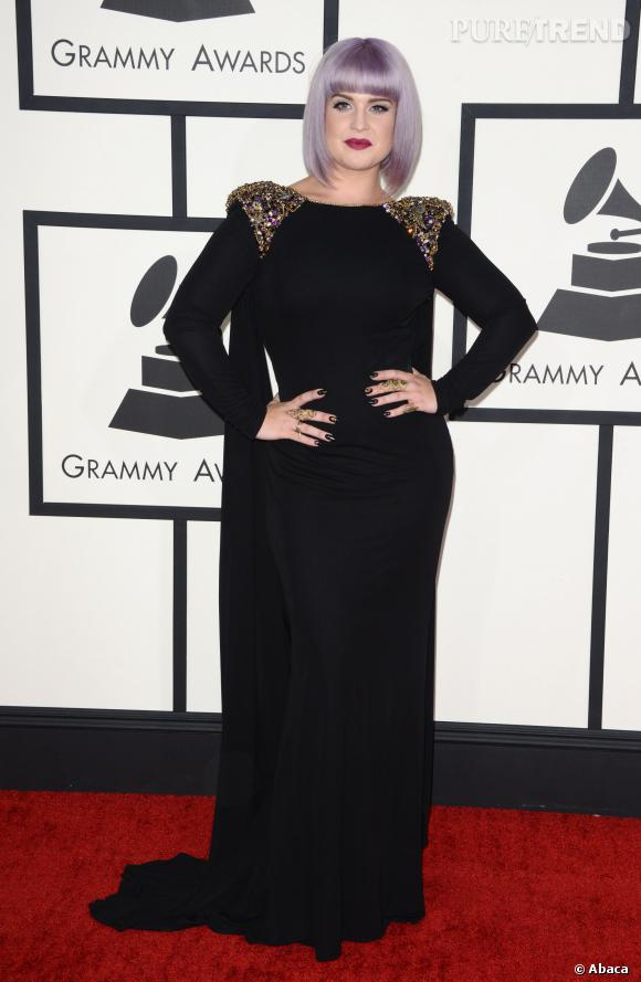Kelly Osbourne très élégante dans une robe fourreau noire et épaulettes sequins sur le tapis rouge de la 56e cérémonie des Grammy Awards.