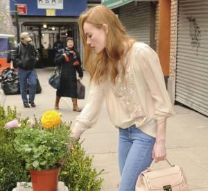 Kate Bosworth ôte son manteau et dévoile une blouse couleur crème.